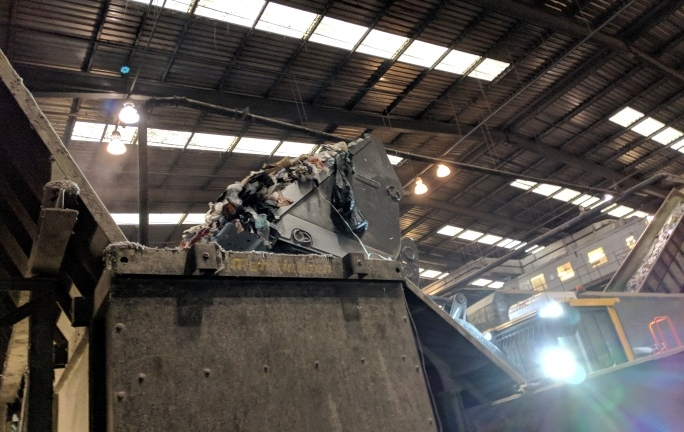 A bucket loader takes mixed feedstock from the tipping hall and places it into the hopper which sends it up the MRF conveyor belt