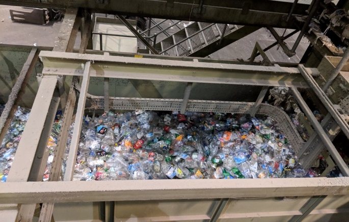 The sorted materials are sent by type along a further conveyor belt to be baled (picture of plastics being sent to baler)